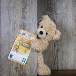 Ein süßer Teddybär, der einen 50€ Schen hält.